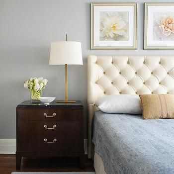 cream tufted leather headboard with a dark stained nightstand