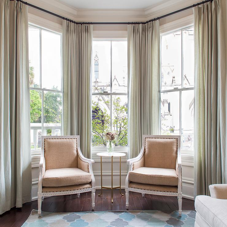 sophisticated sitting room features a bay window dressed in gray green