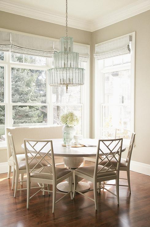 Chic Monochromatic Breakfast Room Features A Turquoise Glass Tiered Chandelier Illuminating Round Dining Table Lined With An Upholstered Bench And