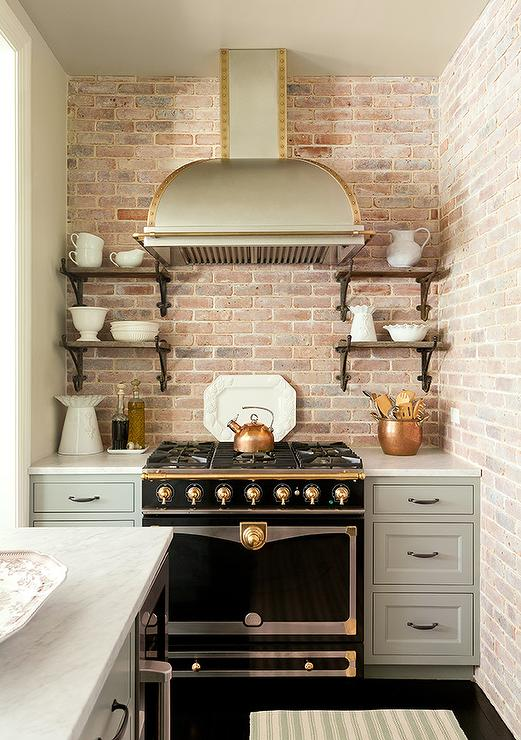 Amazing Kitchen Features A Nook Lined With Exposed Brick Walls Filled With  A Stainless Steel Dome Hood With Brass Trim Over A Black And Gold French  Stove, ...