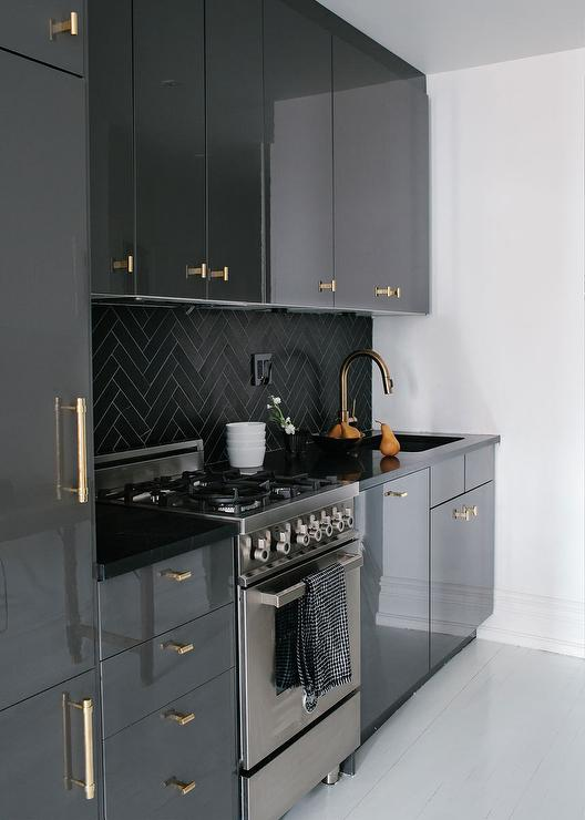 Amazing Kitchen Features Gray Lacquered Cabinets Adorned With Gold Pulls Paired With Black Countertops And A Black Herringbone Tiled Backsplash