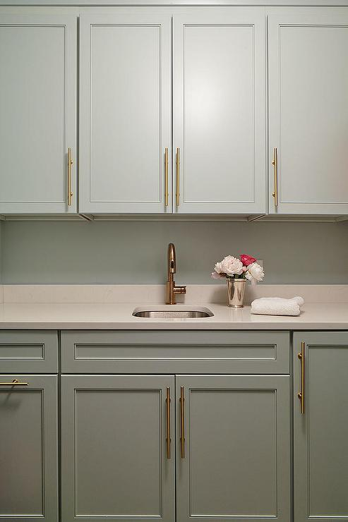 Gray laundry room cabinets with long brass pulls for Long kitchen cupboard