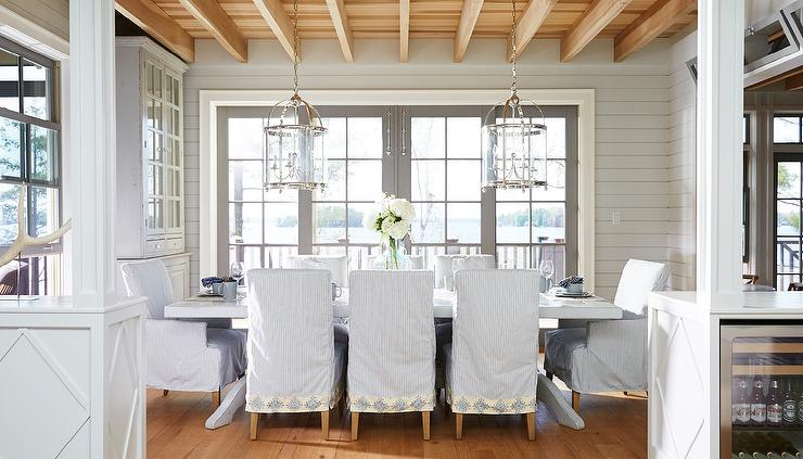 Chic Cottage Dining Room Is Filled With A Whitewashed Table Lined Ticking Stripe Slipcovered Chairs Illuminated By Two Round Lanterns