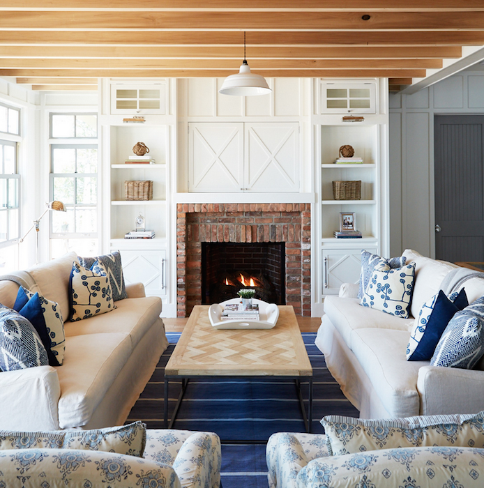 Cottage living room features a pair of white slipcovered sofas adorned with blue pillows facing each other across from a chevron tiled coffee table atop a blue striped rug.