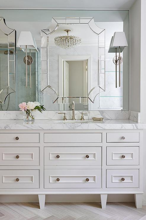 Exquisite bathroom boasts a white footed custom washstand adorned with  nickel knobs topped with calacatta marble fitted with his and hers sinks  and ...