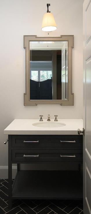 amazing powder room features a gray beaded mirror illuminated by a cone sconce situated over a black single washstand topped with white quartz alongside a - Powder Room Vanities