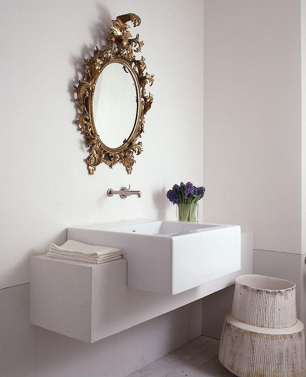 Chic Powder Room Features A Gold Oval Baroque Mirror Over Wall Mount Faucet And Concrete Vanity Ed With White Porcelain Sink