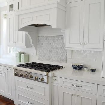 Hexagon Marble Backsplash In Kitchen With Curved Glass Hood Vent