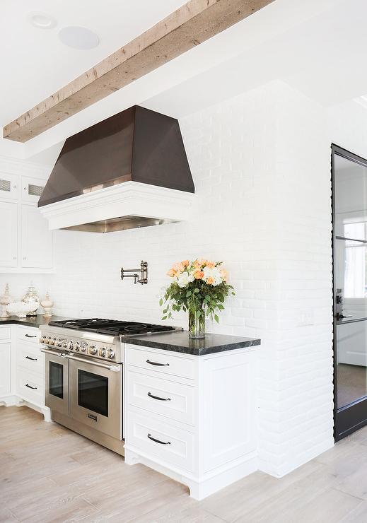 white and black kitchen with white exposed brick backsplash