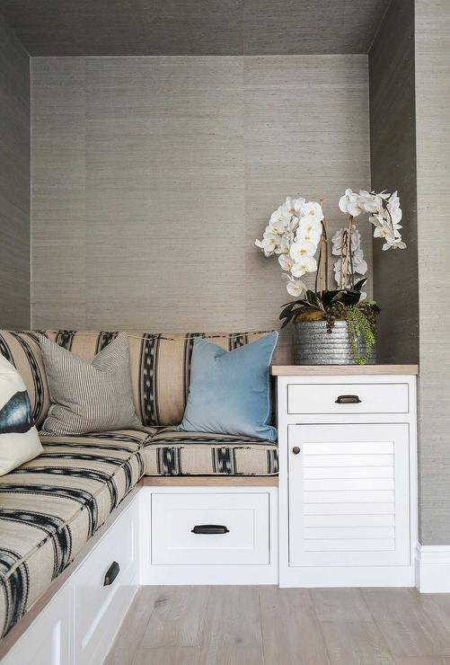 Living Room Nook Is Clad In Gray Grasscloth Wallpaper And Filled With A L  Shaped Built In Bench Covered In Taupe And Black Fabric.