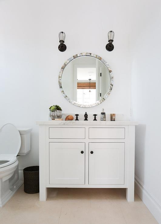 white bathroom cabinets with bronze hardware. chic powder room boasts a round capiz shell mirror illuminated by bronze cage sconces over white vanity adorned with oil rubbed knobs topped bathroom cabinets hardware