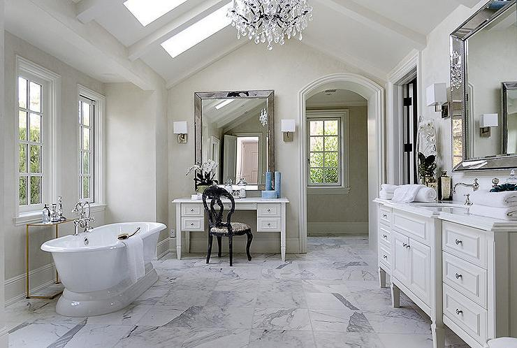 Master Bathroom Features A Vaulted Ceiling Fitted With Skylights And Crystal Chandelier Illuminating Freestanding Oval Tub Placed Under Windows Facing