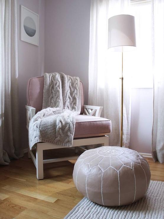 Purple and grey bedroom features a corner reading space boasting a purple  chair draped in a gray knitted throw and a purple leather Moroccan pouf ...