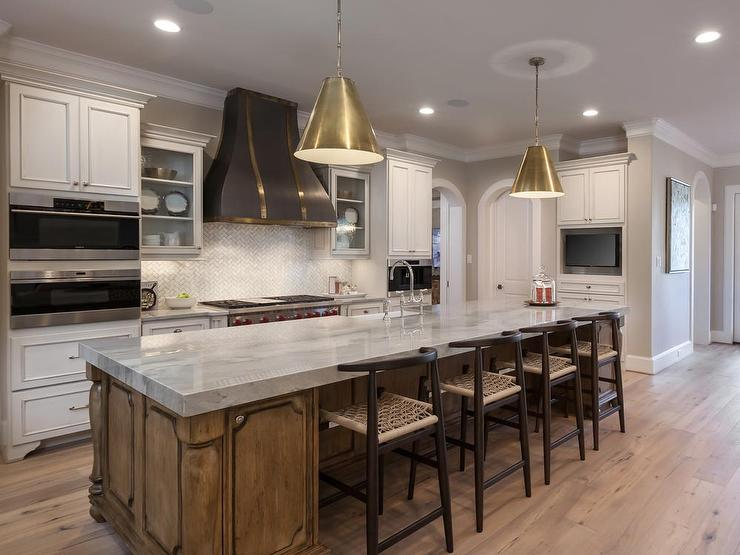 Stunning Kitchen Features A Pair Of Goodman Hanging Lamps In Antique Brass  Illuminating A Brown Stained Center Island Topped With Gray And White  Quartzite ...