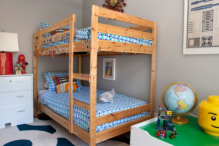 boys room features a pine bunk bed dressed in blue polka dot bedding next to a white dresser as nightstand atop a navy and beige rug bunk beds kids dresser