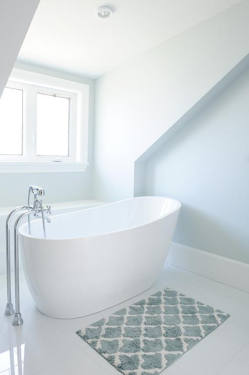 White And Blue Bathroom With Blue Bath Mat Placed In Front Of An Oval  Freestanding Tub And A Vintage Style Floor Mount Tub Filler.
