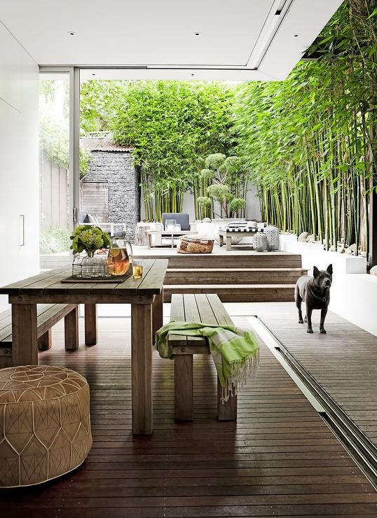 Zen Covered Patio Is Filled With A Rectangular Teak Outdoor Dining Table Lined Matching Benches Next To Steps Which Lead An Open Deck
