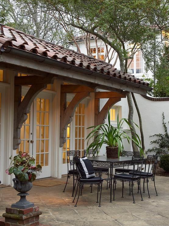 Wrought Iron Outdoor Dining Table Part - 32: A Wall Of Transom Windows And French Doors Open To A Patio Filled With A Wrought  Iron Greek Key Dining Table And Chairs.