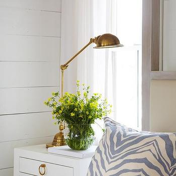 white nightstand with gold ring pulls and antique brass task lamp