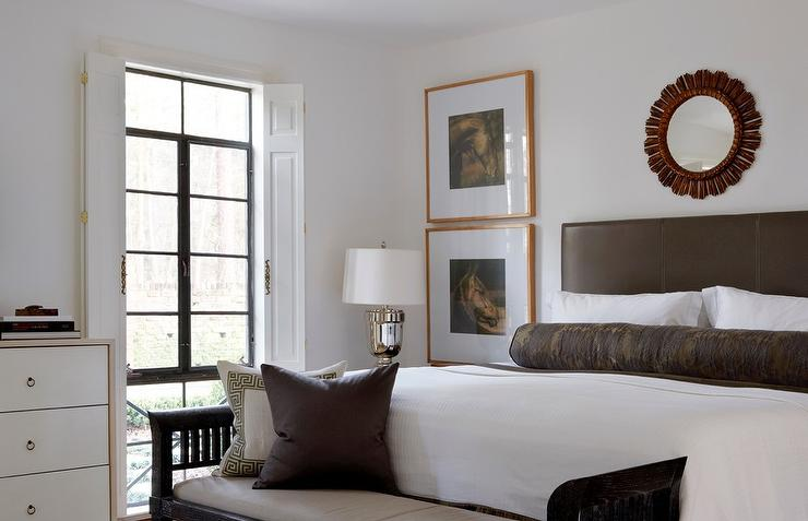 chic bedroom features a red sunburst mirror above a brown leather headboard on bed dressed in soft white bedding a long brown bolster pillow next to a