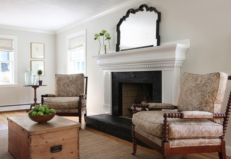 Cottage living room features a white fireplace mantle with dentil moldings accented with a black brick surround and a black brick hearth flanked by a pair of brown spindle chairs upholstered in taupe floral fabric across from a trunk coffee table atop a t
