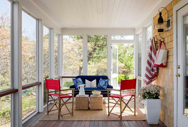 Sunroom With Blue Sofa And Red Chairs
