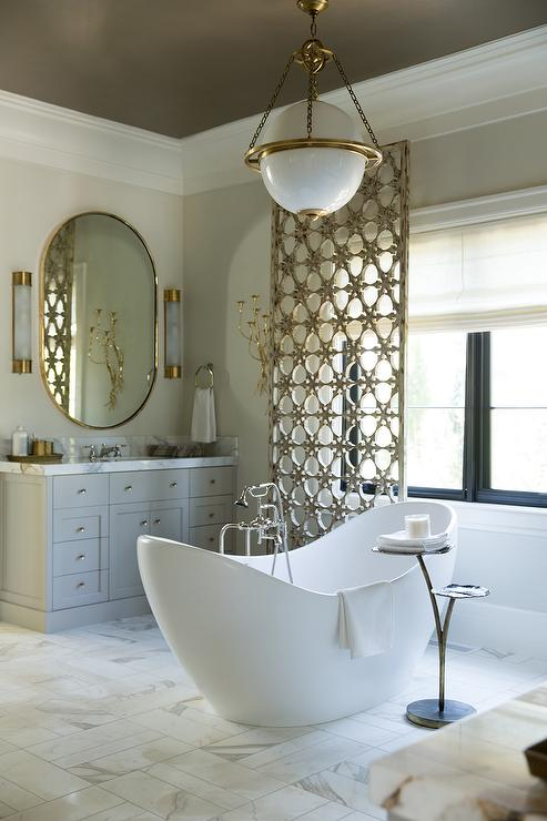 Exquisite Bathroom Features A Taupe Ceiling Accented With An E F Chapman Modern  Globe Pendant Suspended Over An Egg Shaped Tub And A Floor Mount Tub Filler  ...