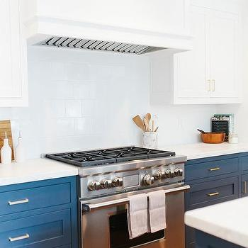 Blue kitchen features white upper cabinets and navy lower cabinets