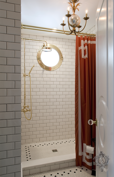 Fabulous bathroom features a open walk in shower filled with white subway  tiles accented dark grout framing gold porthole window as well Black Shower Curtain Design Ideas