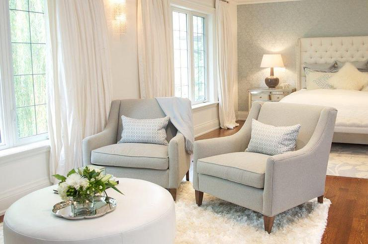 bedroom sitting area with gray chairs and white ottoman transitional
