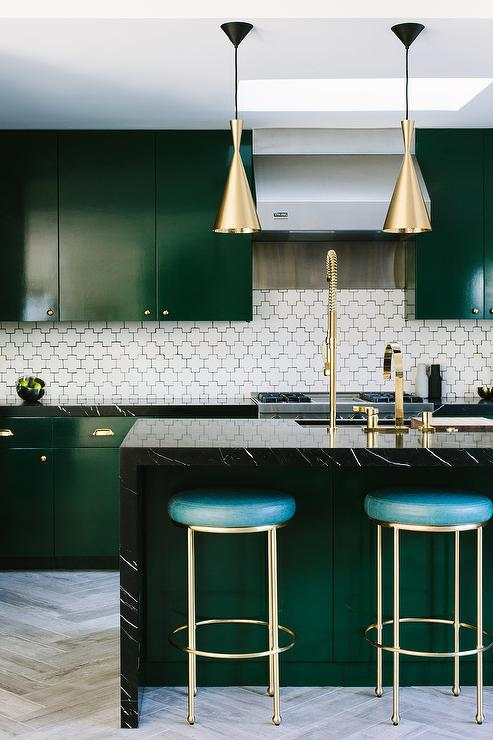 Lovely kitchen features emerald green flat front cabinets adorned with