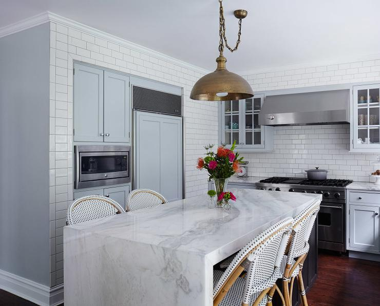 white marble waterfall island with copper pendant transitional kitchen