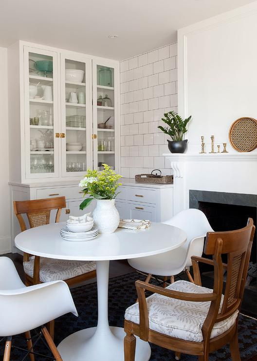 Eat In Kitchen Features An Ikea Docksta Table Lined With Mid Century Modern Dining Chairs And Saarinen Tulip Armchairs Placed Front Of A White Fireplace