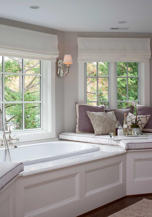 Elegant bathroom features a bay window filled with a wainscoted corner tub  flanked by window seats adorned with gray and purple pillows under windows  ...