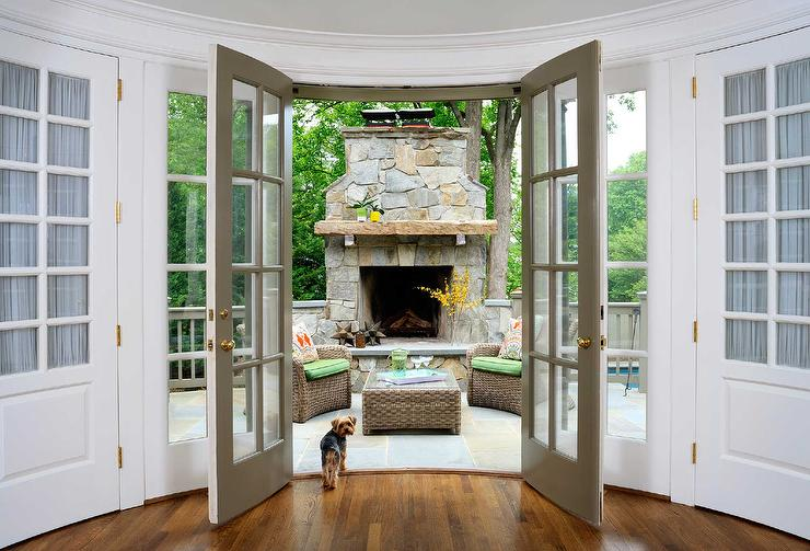 Grey French Doors Open To A Patio Filled With Stone Fireplace Hearth Alongside Pair Of Wicker Chairs Green Cushions Facing Each Other Across