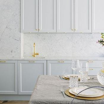 White Kitchen Cabinets With Brass Hardware And Marble Backsplash