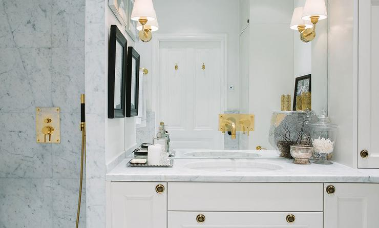 White And Gold Bathroom Features A White Vanity Adorned With Brass Ring  Pulls Topped With Carrera Marble Under A Full Height Mirror Lined With A  Brass ...