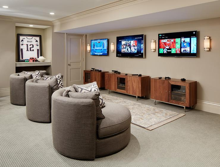 Basement Game Room Features Three Gray Swivel Chairs, Room And Board Eos  Swivel Chairs, Adorned With Grey Pillows Facing A Row Of Flatscreen TVs  Placed ...