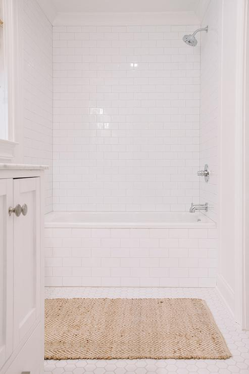 kidsu0027 bathroom features a dropin tub tiled with subway tiles alongside a white hex floor lined with a west elm jute chenille herringbone rug