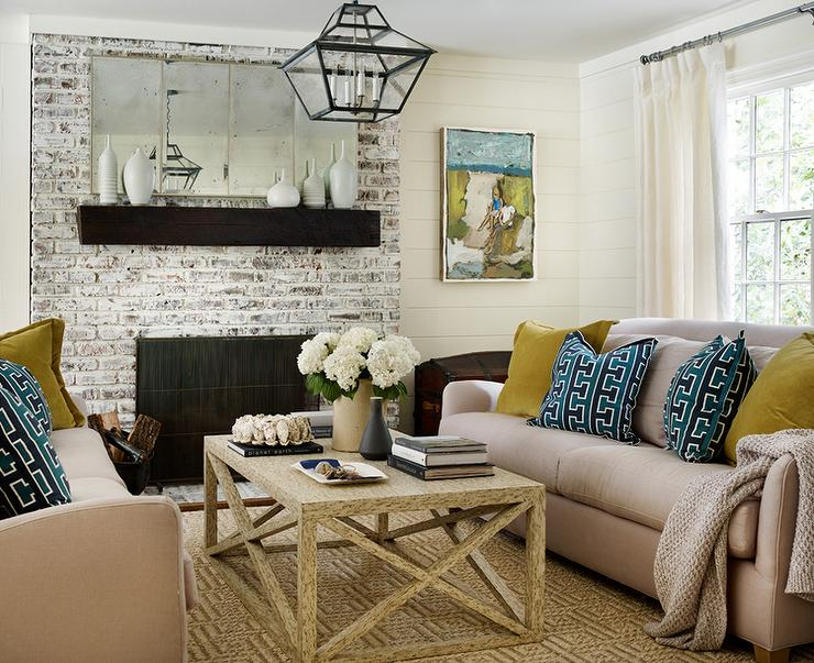 Beautiful living room features taupe sofas lined with peacock blue geometric pillows facing each other across from a wood x based coffee table placed in front of a whitewashed brick fireplace lined with a dark stained chunky mantle and an antiqued mirror.
