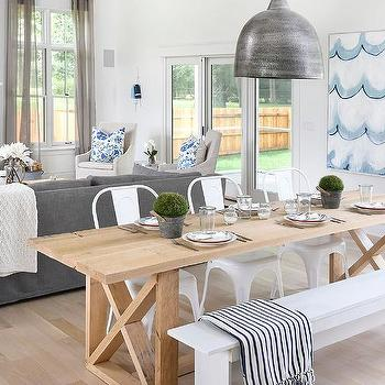 blond x based dining table with white tolix chairs