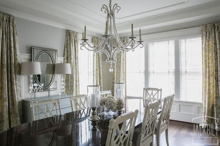 Elegant Dining Room Features A Chippendale Table Lined With White French Chairs Illuminated By An E