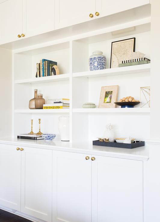 Chic Living Room Features White Built In Shelves Sandwiched Between Cabinets Adorned With Brass Octagon Knobs