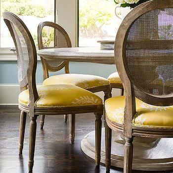 Round Marble Top Dining Table With Cane Back Chairs And Yellow Seat Cushions