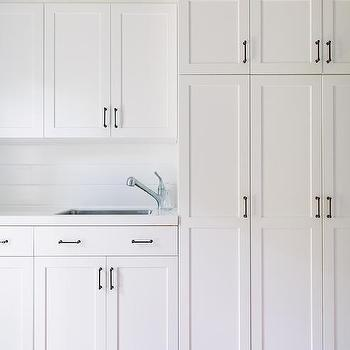 White Laundry Cabinets With Bronze Pulls Design Ideas