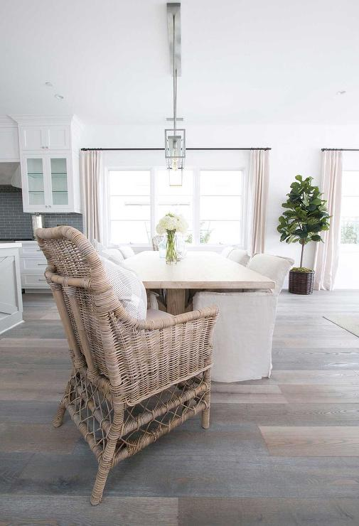 Oceanside dining room features a glass and nickel rectangular box  chandelier illuminating a light wood reclaimed wood dining table lined with  natural linen ...