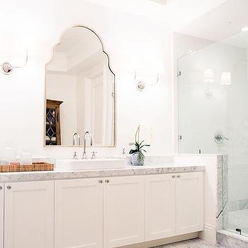 'White Shaker Bathroom Cabinets with Carrera Marble Countertop' from the web at 'https://cdn.decorpad.com/photos/2015/09/19/m_white-vanity-shaker-cabinets-vendome-double-sconce-chevron-bath-rug.jpg'