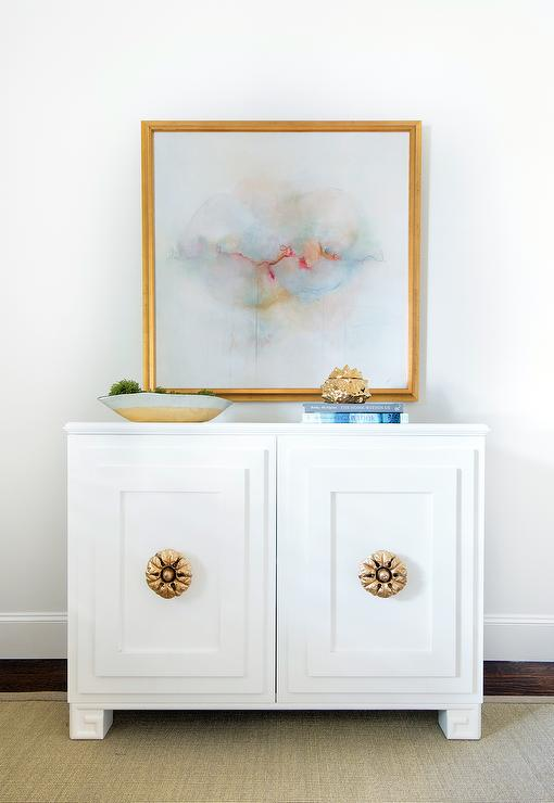 White Cabinet With Gold Pulls And Pastel Colored Abstract Art