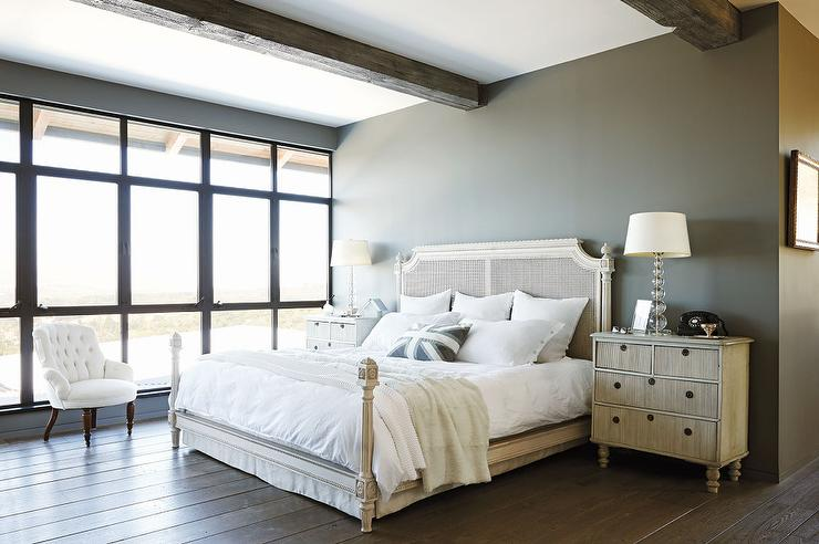 Modern French bedroom features rustic wood beams over a white cane bed  dressed in plush white bedding and an union jack pillow flanked by French  nightstands. Modern French Bedrooms Design Ideas