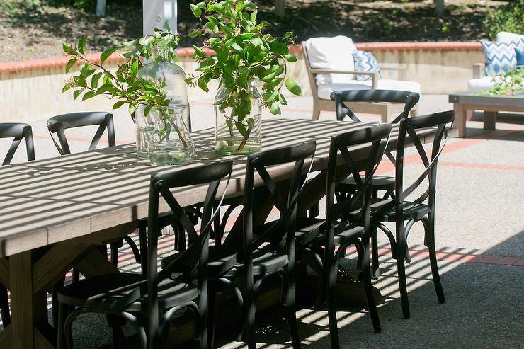 gray x based outdoor dining table with black french cafe chairs
